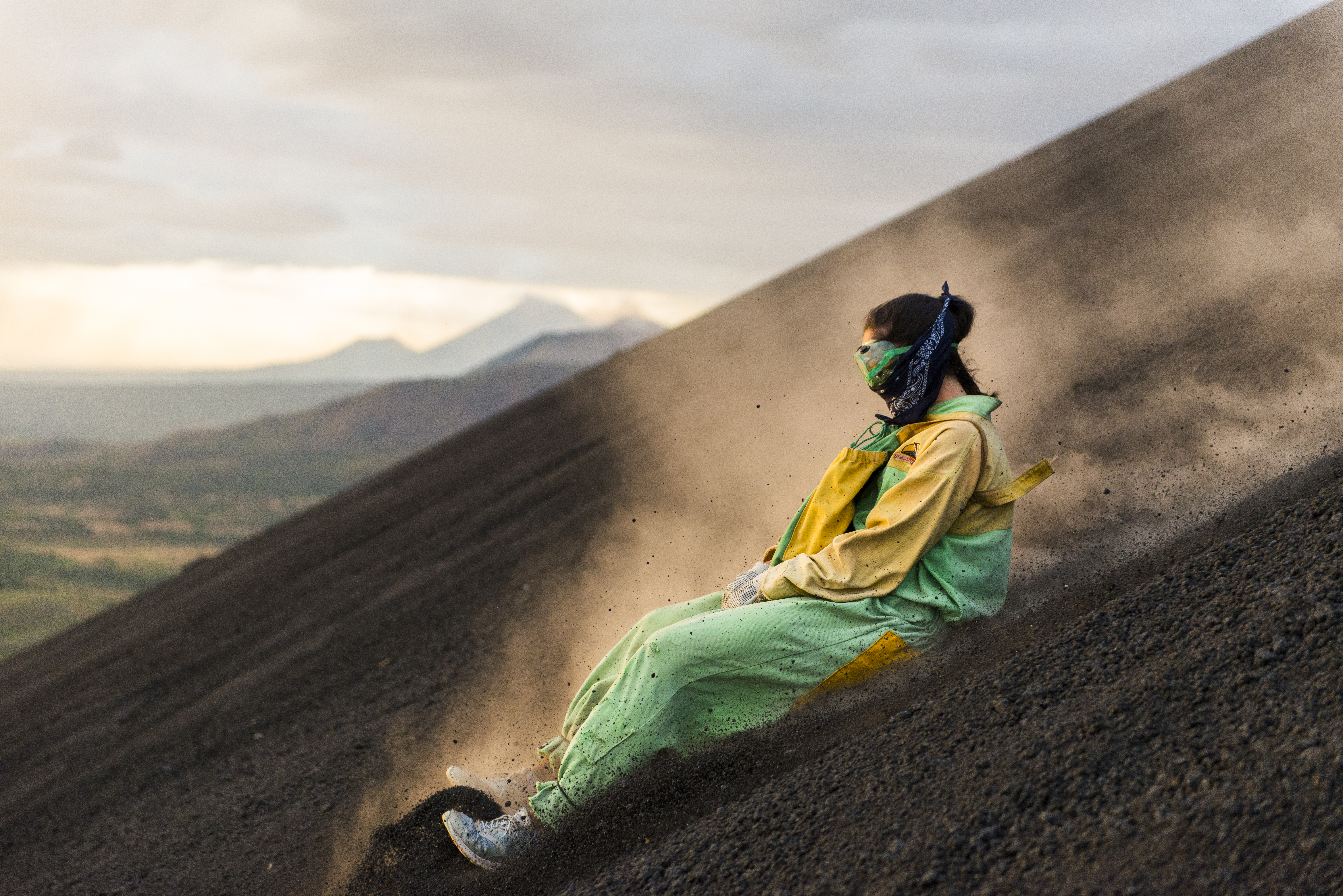 Frau fährt mit dem Surfbrett vom Vulkan Cerro Negro, Cordillera de los Maribios, Leon, Nicaragua