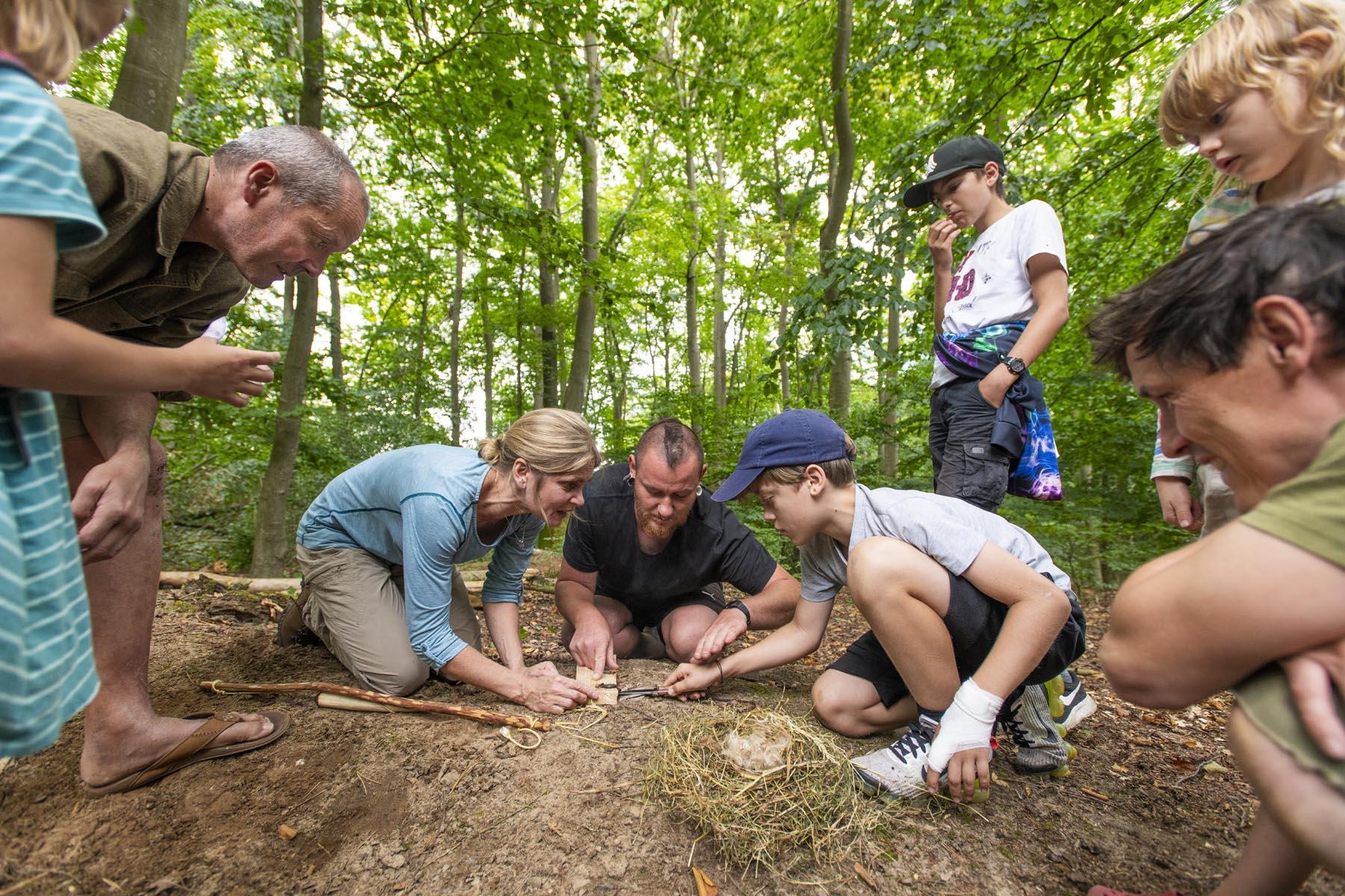Teilnehmer der Wildnisschule Uckermark üben das Feuermachen mit dem Feuerbogen.