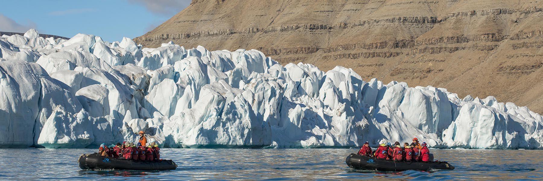 Schlauchboot mit Passagieren von One Ocean Expeditions vor Croker Gletscher, Croker Bay, Devon Island, Nunavut, Arktis, Kanada
